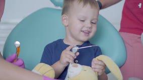 坐在椅子的小无忧无虑的男孩在牙齿办公室 使用与豪华的玩具的逗人喜爱的孩子 牙齿治疗,医疗 股票录像