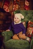坐在椅子的小男孩在壁炉附近 免版税库存照片