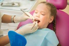 坐在椅子的小逗人喜爱的女孩在牙医诊所在牙齿核对和治疗,特写镜头画象期间 库存照片