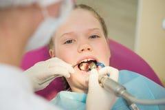 坐在椅子的小逗人喜爱的女孩在牙医诊所在牙齿核对和治疗,特写镜头画象期间 免版税库存图片