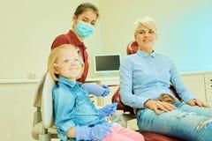 坐在椅子的小逗人喜爱的女孩在牙医 免版税库存图片