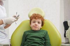坐在椅子的小逗人喜爱的男孩在牙医 库存图片