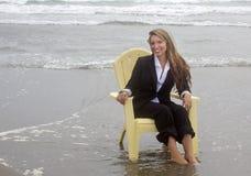 坐在椅子的微笑的妇女在海洋 免版税库存图片
