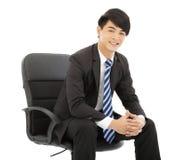 坐在椅子的微笑的年轻商人 免版税库存照片