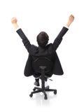 坐在椅子的成功的激动的商人 免版税库存图片
