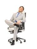 坐在椅子的新生意人 免版税图库摄影