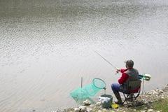 坐在椅子的渔夫在河沿卷的串和投掷的标尺入河 免版税库存照片