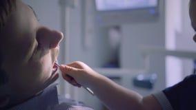 坐在椅子的特写镜头画象少年人在牙医办公室,当扮演医生的逗人喜爱的孩子,检查他的时 股票录像