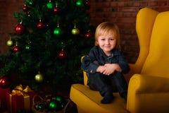 坐在椅子的男孩在圣诞树附近 免版税库存图片