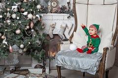 坐在椅子的矮子服装的小男孩在家内部壁炉和等待的圣诞老人 免版税库存照片