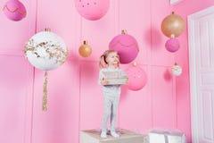 坐在椅子的逗人喜爱的小女孩和打开有一个礼物的一个箱子背景与装饰品的圣诞树的 的treadled 库存照片