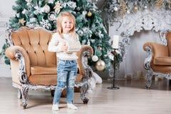 坐在椅子的逗人喜爱的小女孩和打开有一个礼物的一个箱子背景与装饰品的圣诞树的 免版税图库摄影