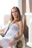 坐在椅子的年轻美丽的妇女 免版税库存照片