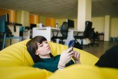 坐在椅子袋子的一个美丽的年轻办公室工作者的画象和使用电话 反对后台作业 免版税库存图片