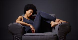 坐在椅子认为的黑人妇女 图库摄影