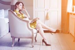 坐在椅子阅读书的年轻红头发人妇女 免版税库存图片