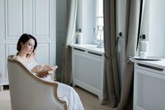 坐在椅子阅读书的年轻红头发人妇女 库存图片