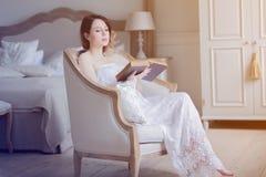 坐在椅子阅读书的年轻红头发人妇女 免版税库存照片