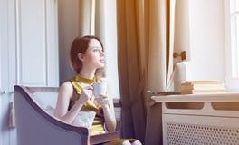 坐在椅子阅读书的年轻红头发人妇女 图库摄影