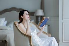 坐在椅子阅读书的年轻红头发人妇女 库存照片
