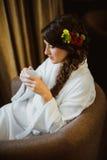 坐在椅子饮用的咖啡的新娘 免版税库存图片
