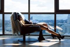 坐在椅子,她的脚的妇女在窗口 免版税库存图片