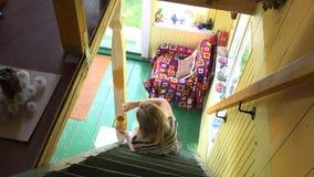 坐在楼梯和绘的木专栏杆的妇女与黄色颜色刷子 4K 股票录像