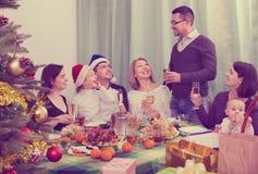 坐在欢乐桌上的多代快乐的家庭 免版税库存图片