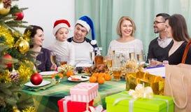 坐在欢乐桌上的多代愉快的微笑的家庭 图库摄影
