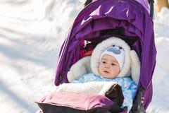 坐在步行的一辆婴儿推车的愉快的男婴 库存照片