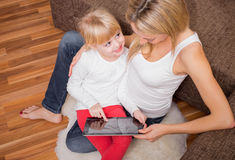 坐在母亲舔和指向片剂的小女孩 免版税库存图片