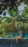 坐在比基尼泳装的可爱的女孩 免版税图库摄影