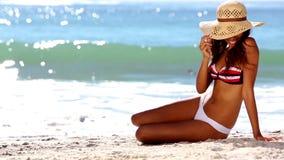 坐在比基尼泳装的可爱的妇女