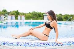 坐在比基尼泳装的美丽的年轻性感的妇女在游泳池旁边 夏天职业 库存图片