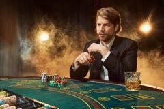 坐在比赛表上的西装的一个人 男性球员 激情,卡片,芯片,酒精,模子,赌博,赌博娱乐场 免版税库存图片