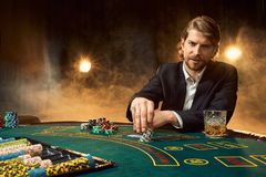 坐在比赛表上的西装的一个人 男性球员 激情,卡片,芯片,酒精,模子,赌博,赌博娱乐场 库存图片