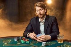 坐在比赛表上的西装的一个人 男性球员 激情,卡片,芯片,酒精,模子,赌博,赌博娱乐场 免版税库存照片