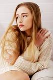 坐在毛线衣的哀伤,担心的美丽的白种人妇女。 免版税库存图片