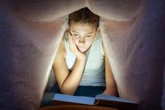 坐在毯子和阅读书下的年轻十几岁的女孩 库存图片