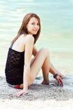 坐在水附近的可爱的少妇 库存照片