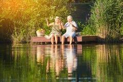 坐在水附近的资深夫妇 免版税库存照片