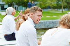 坐在池塘和谈话的商人 免版税库存图片