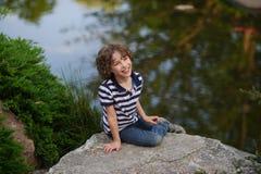 坐在池塘边缘的微笑的男孩 免版税库存照片