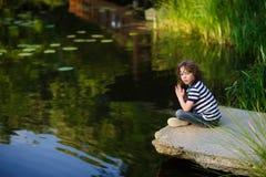 坐在池塘边缘的沉思小男孩 免版税库存图片