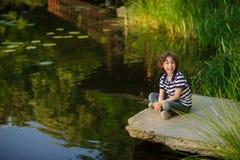 坐在池塘边缘的白肤金发的卷发的男孩 库存照片