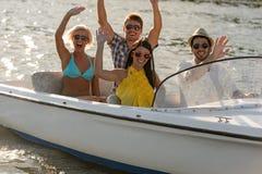 坐在汽艇的挥动的青年人 免版税库存照片