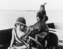 坐在汽艇的十几岁的女孩驾驶被狗(所有人被描述不更长生存,并且庄园不存在 供应商wa 库存照片