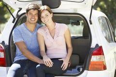 坐在汽车后车箱的夫妇  图库摄影
