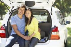 坐在汽车后车箱的夫妇  免版税库存照片