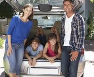 坐在汽车后车箱的家庭  图库摄影